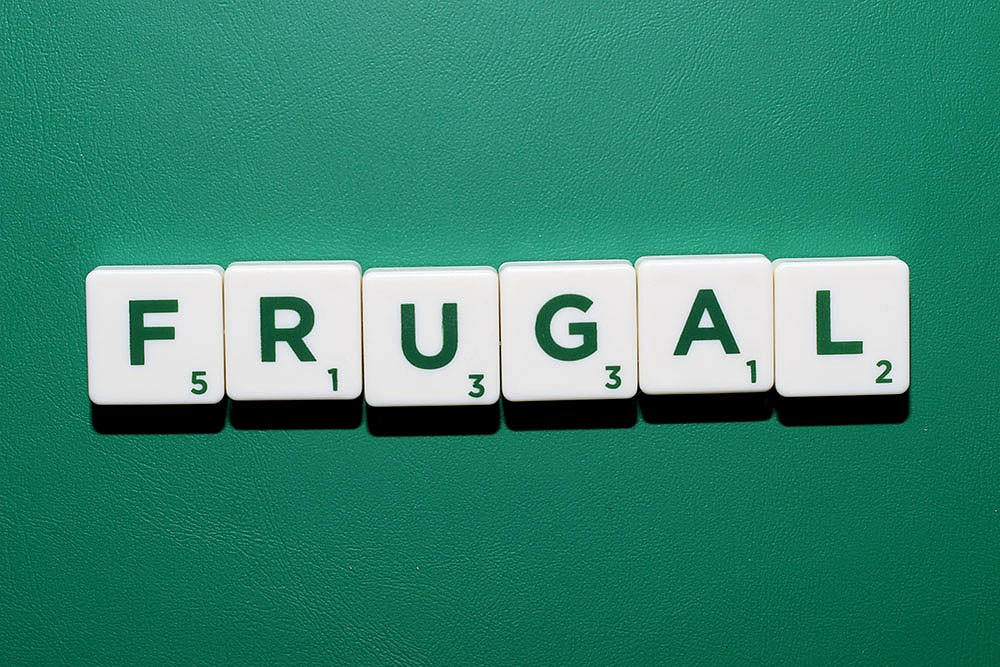 Scrablle tiles spelling out the word frugal which as you will learn, is not the same as cheap. Saving money is fine, cheating others not so much.