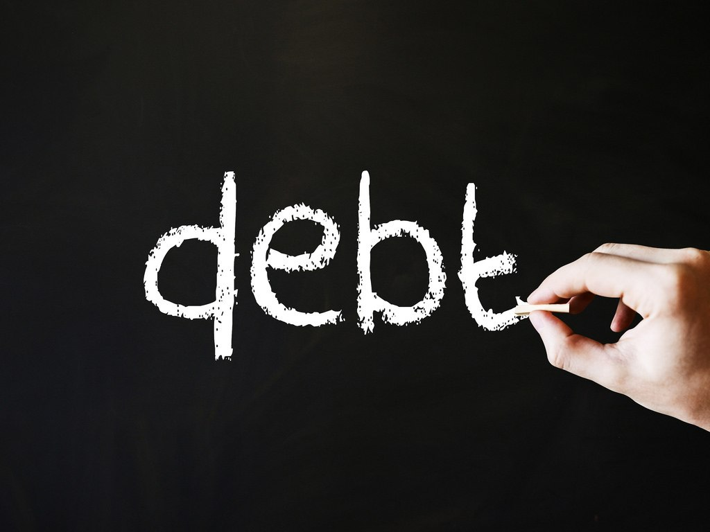 """A hand writing """"debt"""" on the blackboard. You can get out of debt if you want to. We did."""