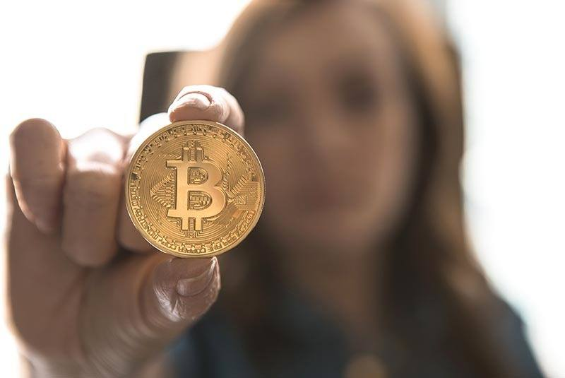 An image of a person examining a bitcoin which is a popular cryptocurrency for people to make money with.