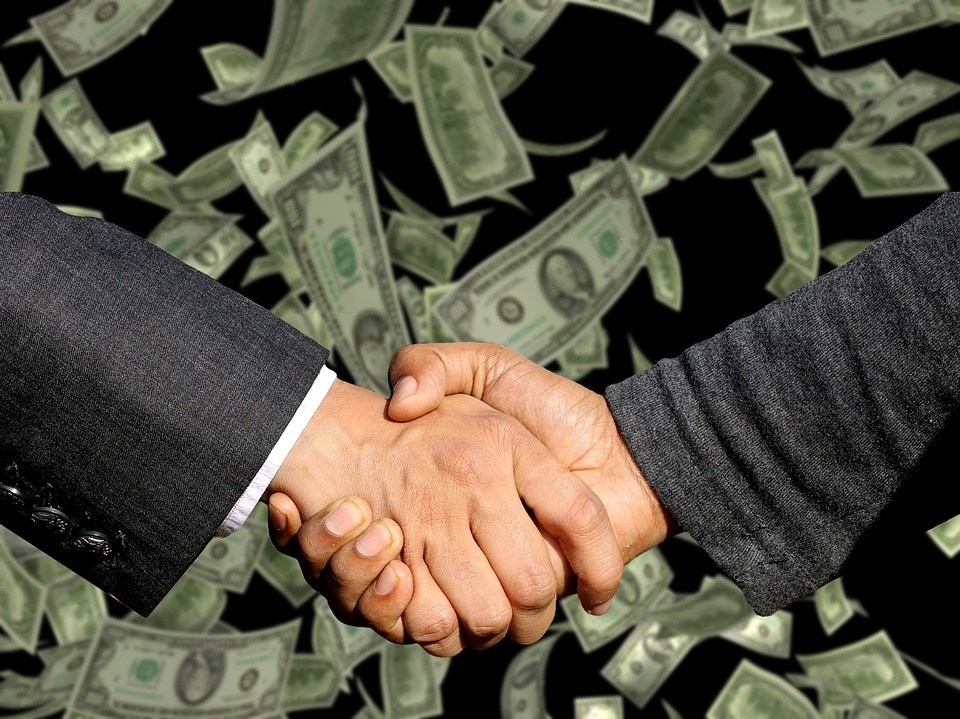 An image of money cascading down as two people reach a commitment for a better life.