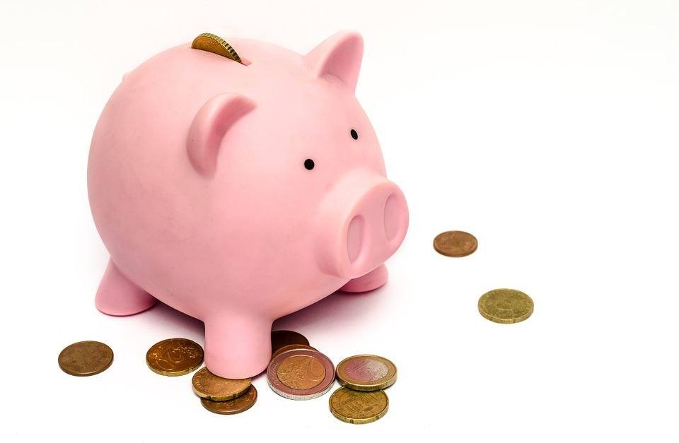A picture of a piggy bank with a few coins in front of it, to symbolize the power of saving money.