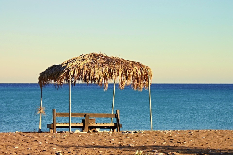 Here we see a bench on a beach a common destination for a mini-retirement when you save enough money to go.
